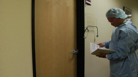 A doctor examines a medical chart and enters a patient's room Footage
