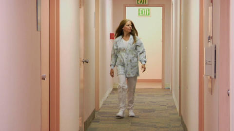 A Medical Professional Walks Down The Hallway Of A Medical Facility stock footage