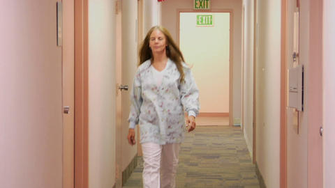 A medical professional walks down the hallway of a... Stock Video Footage