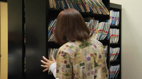 A medical professional retrieves a patient chart from a... Stock Video Footage
