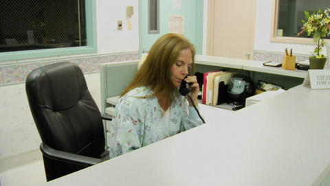 A woman answers a phone behind the information desk of a... Stock Video Footage