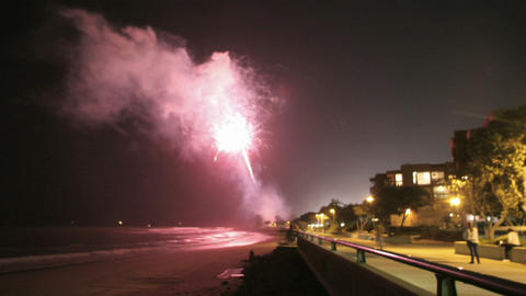Fireworks explode off a beach Footage