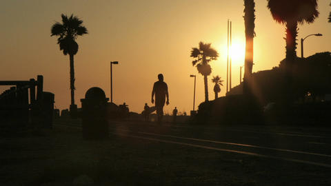 Pedestrians move to and fro on a silhouetted beach front Stock Video Footage
