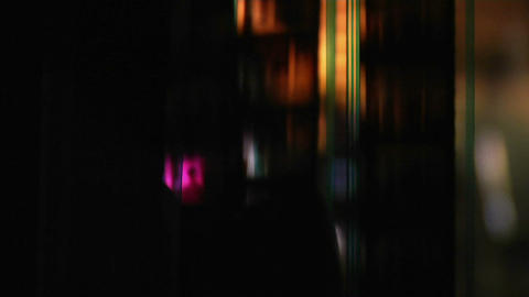 A back-lit strip of film runs through a projector Stock Video Footage
