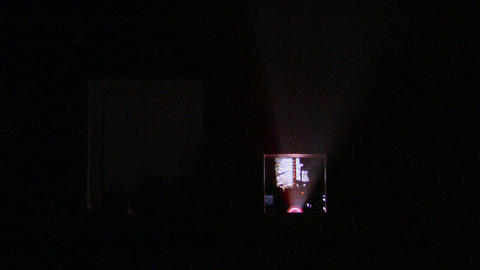 Light shines from a projector into a darkened theater Stock Video Footage