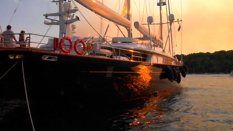 Sunset light reflects on the side of a moored sailboat Footage