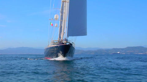 A traveling shot around the bow of a large sailboat at sea Footage
