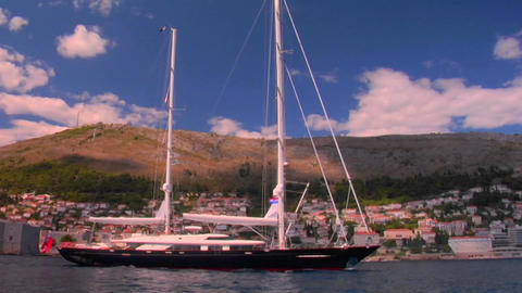 A sailboat sails into a Mediterranean port Stock Video Footage