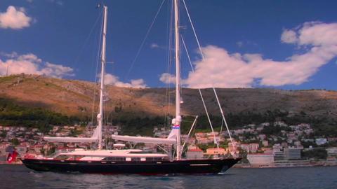 A sailboat sails into a Mediterranean port Stock Video Footage