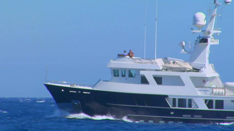 A medium shot of a medium sized boat moving through open ocean Footage