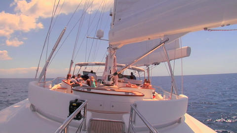 A sailboat sails across the ocean and we look up to the mast and sail Footage