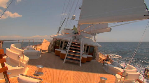 A sailboat travels across the ocean in this view from the aft deck Footage