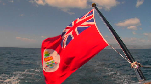 The flag of the Cayman Islands flies behind a ship on the high seas Footage