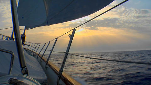 A shot of the side of a sailboat heading into the sunset Footage