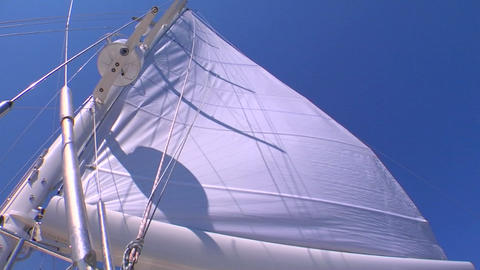 A sail blows in the wind on a sailboat Stock Video Footage