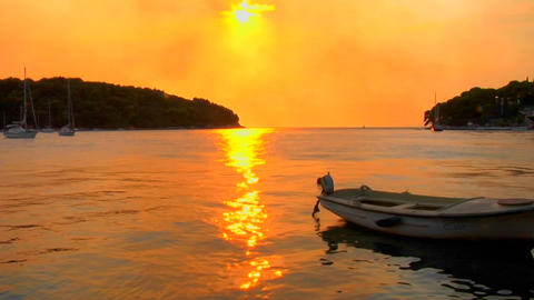 A small boat gently floats as a Croatian sunset transpires Stock Video Footage