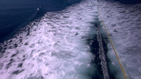The wake of a sailboat passes by as it sails through the calm water Footage