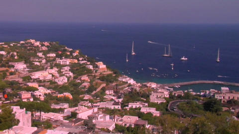 The island of Capri, Italy is visible with ships anchored in the harbor in the distance Footage
