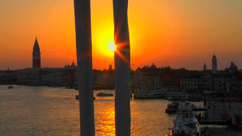 Beautiful silhouetted view of a sunset of Venice, Italy from the mast of a sailboat coming into port Footage