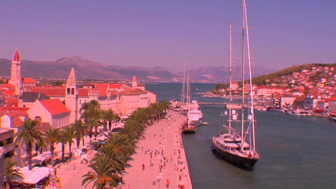 Aerial view of Trojir, Croatia's port and 1000 year old city. People walk along the port as a large Footage