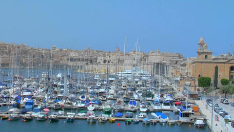 View of Malta's old city scape and ships in the harbor. Zoom out Footage
