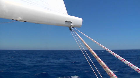 View of boom on sailboat as it sails past blue waters Footage