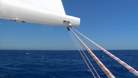 View of boom on sailboat as it sails past blue waters Stock Video Footage