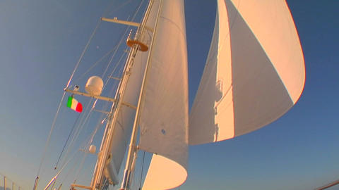 View of sails on sailboat from deck as the wind fills them. Pan down Footage