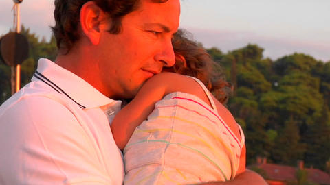 A father holds his daughter in the sunset Footage