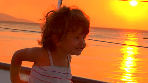A little girl plays on deck in the sunset Stock Video Footage