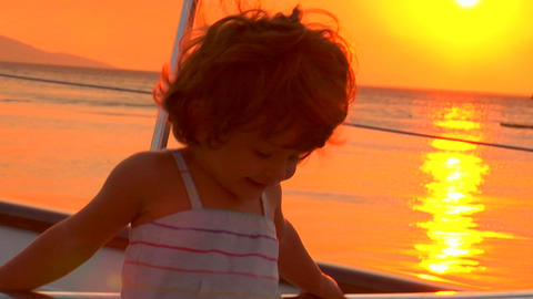 A little girl plays on deck in the sunset Footage