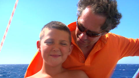 A son and father are affectionate in the wind on a sailboat Footage