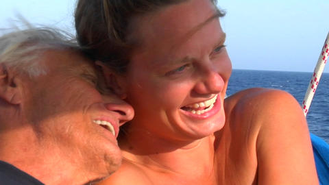 A woman laughs as she hugs an older man on a sailing trip Stock Video Footage