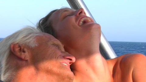 A woman laughs as she hugs an older man on a sailing trip Footage