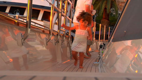 A small child runs down the gunnels of the yacht Stock Video Footage