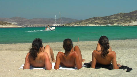 Three ladies sunbathe on a Greek beach Stock Video Footage