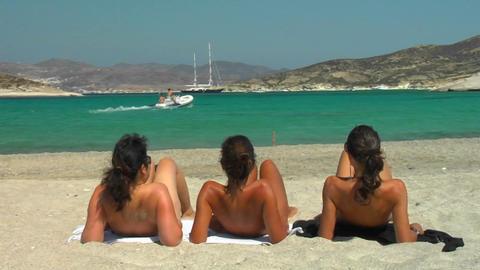 Three ladies sunbathe on a Greek beach Stock Video Footage