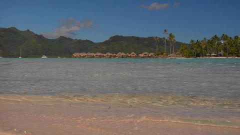 Low angle of Tahitian beach, huts in the distance as... Stock Video Footage