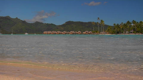 Low angle of Tahitian beach, huts in the distance as waves lap the shore Footage