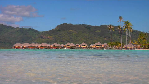 Tahitian huts on the water with lush mountains in the... Stock Video Footage