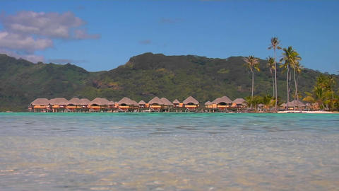 Tahitian huts on the water with lush mountains in the background Archivo