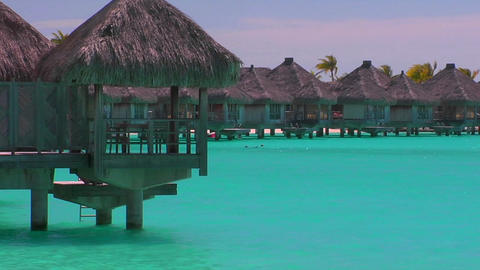 Tahitian huts rest over turquoise water. Slow zoom in Stock Video Footage