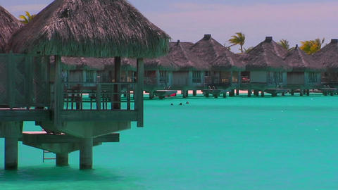 Tahitian huts rest over turquoise water. Slow zoom in Footage