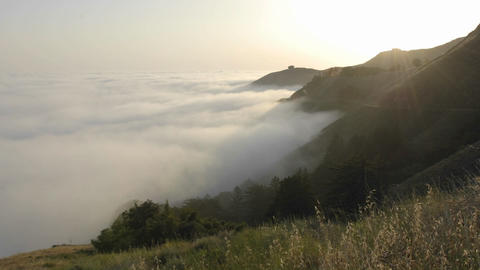 Time lapse of sun setting over fog rolling against the... Stock Video Footage