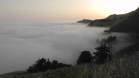Time lapse of sun setting over fog rolling against the mountains at Big Sur, California Footage