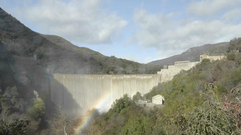 Wide time lapse of a rainbow moving across water spilling over the Matilija Dam after a rain in Ojai Footage