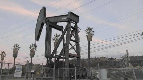 Oil pumpjack increasing speed while pumping in Ventura,... Stock Video Footage