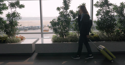 Woman with suitcase talking on phone and walking in airport terminal Footage
