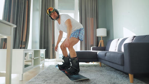 Fun video. Man in shorts and a T-shirt depicts snowboarding on a carpet in a Live Action