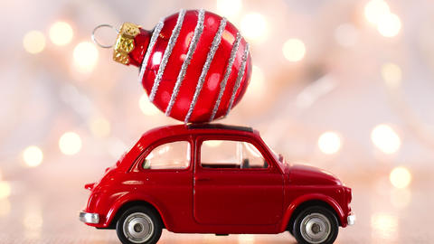 Red little car with Christmas red ornament on the roof and blinking lights behind Live Action